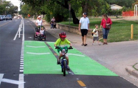 Kid on bike in green-painted bike lane