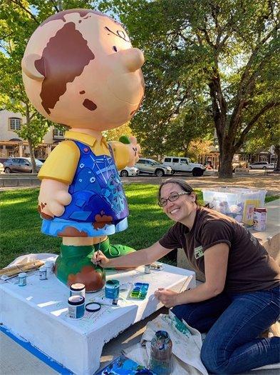 Artist Amber Rankin painting Charlie Brown statue