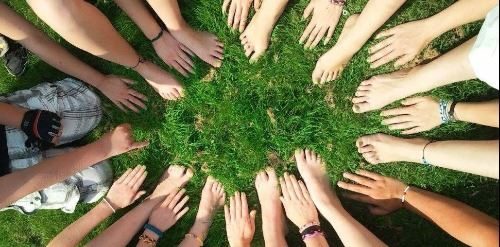 Picture of many hands and feet arranged in a circle on grass
